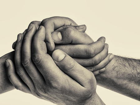 Men's hands hold the female palm on isolated, toned background. That could mean help, guardianship, protection, love, care etc.
