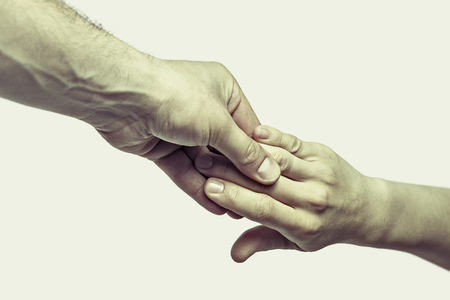 Male hand holds the female palm on light, isolated,  background. That could mean help, guardianship, protection, love, care etc. This Image isolated for easy  transfer in your design.