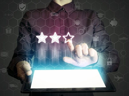 Concept of online rating. Person (man or woman) touches to the three stars (rating icon). Person  holds tablet pc, that contains a many different online services.