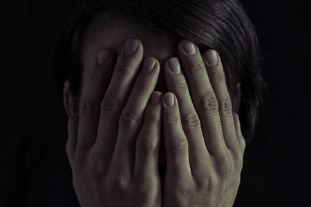 Concept of fear, domestic violence. Woman covers her face her hands. Dim light and black  background , creates a dramatic mood of this  image.