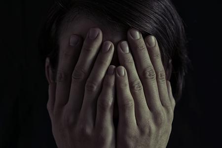 Concept van angst, huiselijk geweld. De vrouw behandelt haar gezicht haar handen. Gedimd licht en een zwarte achtergrond, leidt tot een dramatische sfeer van dit beeld.