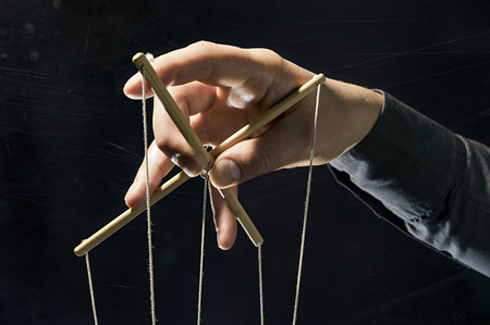 Concept on a theme: the manipulation, the dictator, dependency, slavery, etc. Dictators arm holds  strings for manipulation on black background. Stock Photo