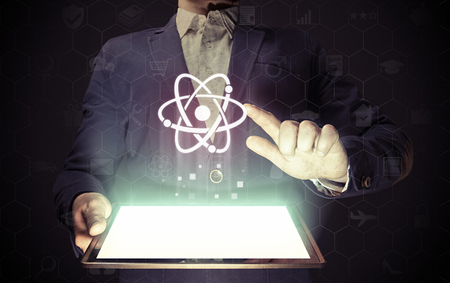 he is different: Concept of scientific and educational online service. Man touches to the atom icon.  He holds tablet pc, that contains a many different online services. Stock Photo
