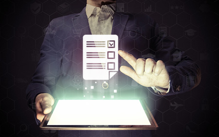 Concept van online testen, vragenlijsten, stemmen. Mens raakt aan vragenlijstpictogram. Hij houdt tablet-pc, die een veel verschillende online diensten bevat.