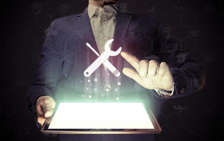 Beeld van een man met tablet pc in zijn handen. Hij drukt op de knop voor technische ondersteuning op virtueel scherm. Het concept van klantenondersteuning, interface-aanpassing, enz.