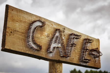 rusty nail: Cafe sign on a wood board, along  road.
