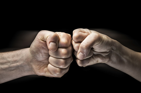 Image close up clash of two fists on black background. Concept of confrontation, competition etc. Standard-Bild