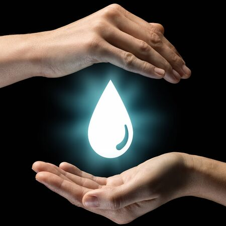 filtración: Isolated image of two hands on black background. Water drop icon in the center, as a symbol of care of water resources. Concept of care of water resources.