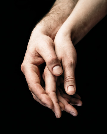A gentle touch of two hands. Concept of LGBT love, caring, tolerance, etc.