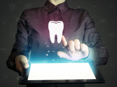 Image of a girl with tablet pc in her hands and tooth icon. Search for dentists, dental services, consultations.