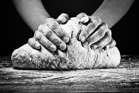Womans hands kneading the dough. In black and white style on dark background.