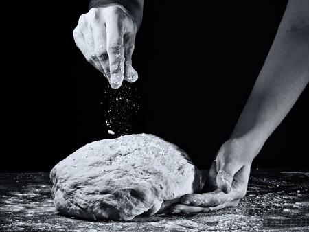 De handen van de vrouw kneden het deeg. In zwart-witte stijl op donkere achtergrond.