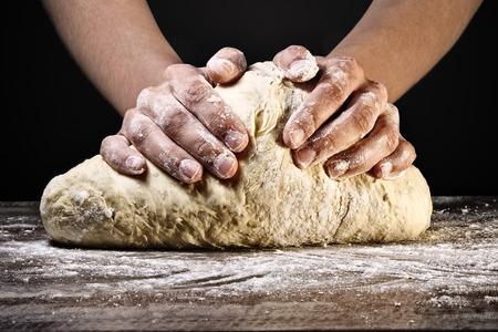 Vrouw handen kneden het deeg, op een donkere achtergrond.