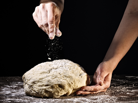 Woman's hands kneading the dough, on dark background.