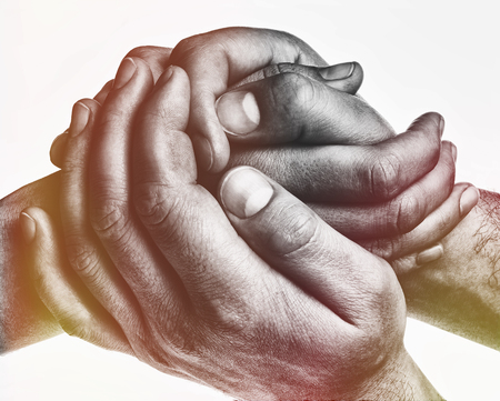 Men's hands hold the female palm on light, toned background. That could mean help, guardianship, protection, love, care etc.
