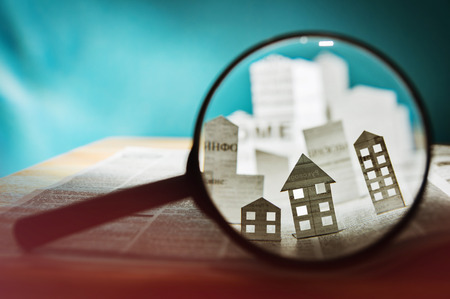 Magnifying glass in front of an open newspaper with paper houses. Concept of rent, search, purchase real estate. Stok Fotoğraf - 83550710