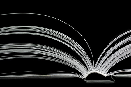 A black and white image of open book. Close-up image of  double-page spread on black background. Concept of gaining knowledge, learning, typography, passion for reading