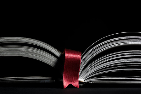 펼친 책의 흑백 이미지입니다. 검은 배경에 빨간색 책갈피와 더블 페이지의 근접 이미지 확대. 지식 습득의 개념, 학습, 타이포그래피, 독서에 대한 열