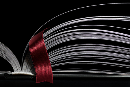 A black and white image of open book. Close-up image of  double-page spread with red bookmark on black background. Concept of gaining knowledge, learning, typography, passion for reading