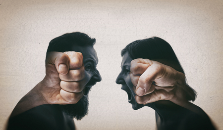 Double exposure image. A man and a woman scream at each other, their silhouettes are combined with a picture of fists to enhance drama. Reklamní fotografie