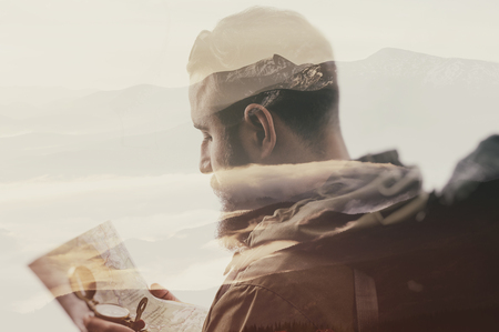 Photo of stylish bearded traveler with a compass and map in hand. Double exposure, beautiful mountain landscape background. Made in vintage style.