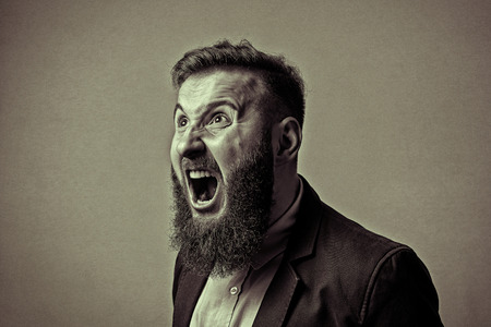 Concept of anger. Bearded man in suit shouts in a state of anger. Black and white image in vintage style. Stock Photo