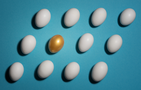 Concept of individuality, exclusivity, better choice. One golden egg among white eggs which are disposed in the diagonal rows on blue background.