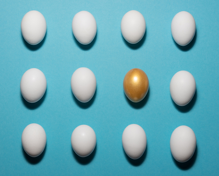 Concept of individuality, exclusivity, better choice. One golden egg among white eggs which are disposed in the right rows on blue background. Stock Photo