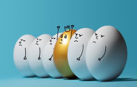 Concept van individualiteit, exclusiviteit, betere keuze en winnen. Een glimlachend gouden ei met een kroon onder boze en droevige witte eieren op blauwe achtergrond. Eieren met grappige getekende gezichten. Stockfoto