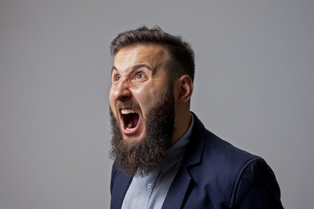 Bearded man in suit shouts in a state of anger. Stock Photo