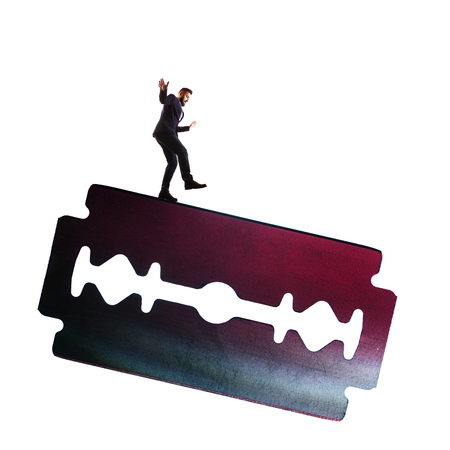 The concept of risk. A man in a business suit is walking along the razors blade. Isolated on white.