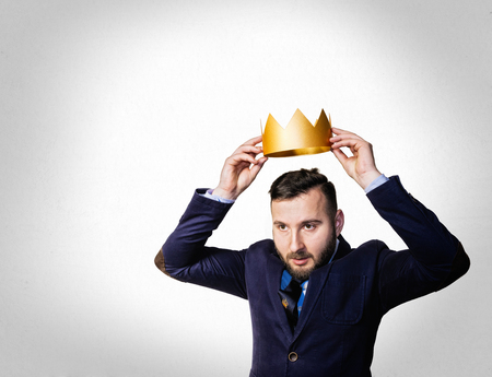 The concept of leadership, excellence. A portrait of a bearded man, he dresses a golden crown on his head.