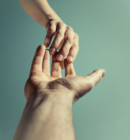 Emotional photo of two hands at the moment of farewell. The concept of breaking relations. Stock Photo