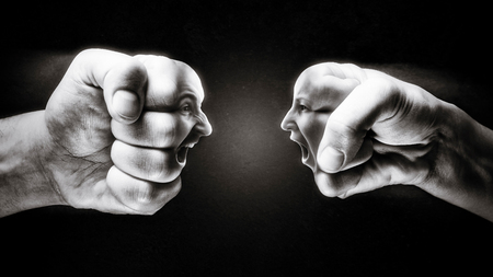 Two fists with a male and female face collide with each other on dark background. Concept of confrontation, competition, family quarrel etc. Black and white.