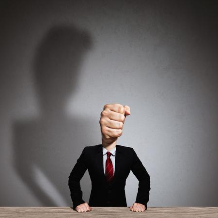 The man in a suit with a head in the form of a fist. Metaphor of an angry boss.