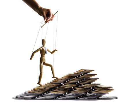 The puppet is climbing on mountain of coins. Concept of success. Isolated on white. Stock Photo