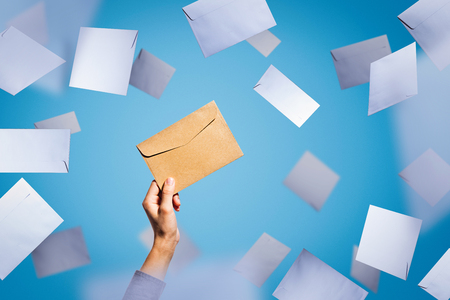 A female hand holds an envelope on a background of falling white envelopes Stock Photo