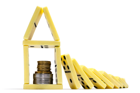 Concept of financial crisis. Domino is falling on bank with money. On isolated white background.