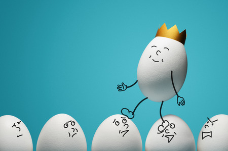 Concept of ambitiousness, careerism. An egg with golden crown walks through heads the white eggs.