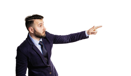 Portrait of a bearded man in a suit on isolated white background. He points emotionally with his finger.