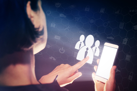 Image of a woman with a smartphone in her hands. She is pressing on the candidates icon. Business recruitment or hiring photo concept. Looking for talent. Standard-Bild
