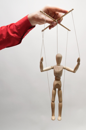 Concept of control. Marionette in womans hand. Stock Photo