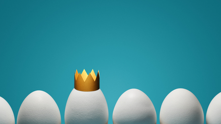 Concept of individuality, exclusivity, better choice. One white egg with golden crown among white eggs on blue background. Stock Photo