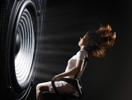 The sound wave set back an office chair with young woman. Stock Photo