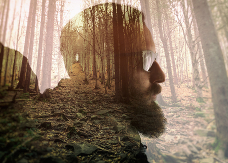 Double exposure with bearded traveler and dense forest. Metaphor of travel and camping.