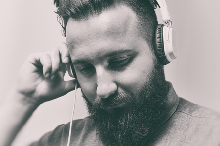 Black and white portrait of a bearded man with a stylish haircut and headphones.