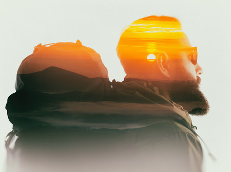 Double exposure with bearded traveler and mountain dawn. Metaphor of travel. Stockfoto