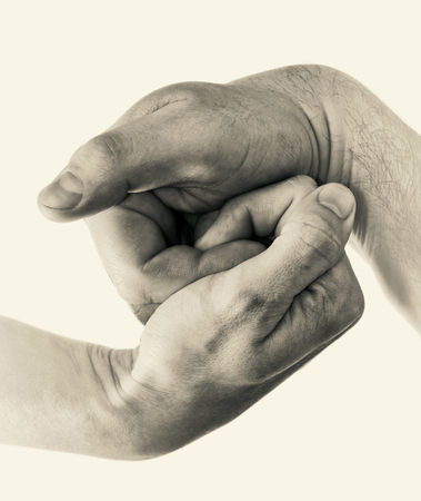 Male and female hands connect with each other. Black and white image.
