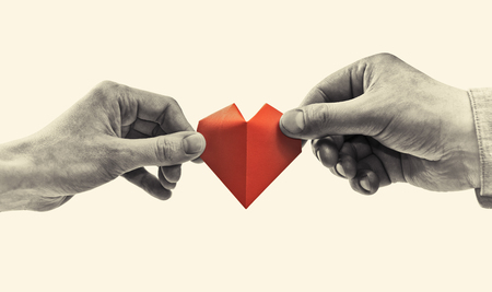 Red heart in woman and man hands. Black and white image. Concept of love,  giving gifts, donorship. Stockfoto