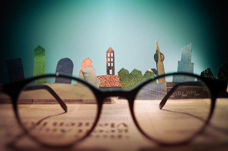 Glasses in front of an open newspaper with paper houses. The concept of renting, searching, buying real estate.
